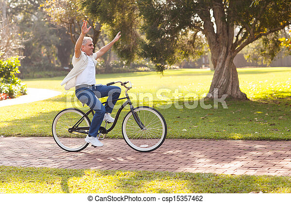 playful middle aged man riding a bike outdoors - csp15357462