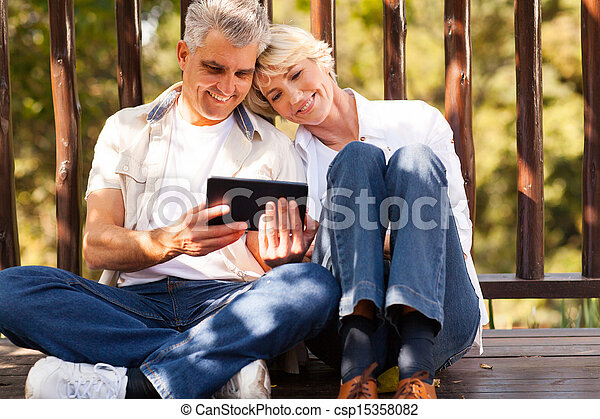 senior couple using tablet computer outdoors - csp15358082