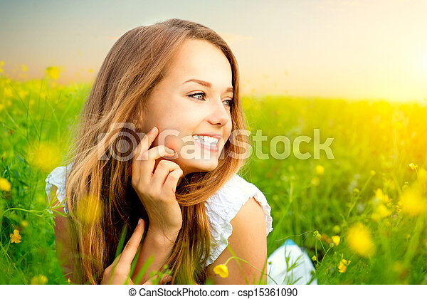 Beauty Girl in the Meadow lying on Green Grass with wild Flowers  - csp15361090