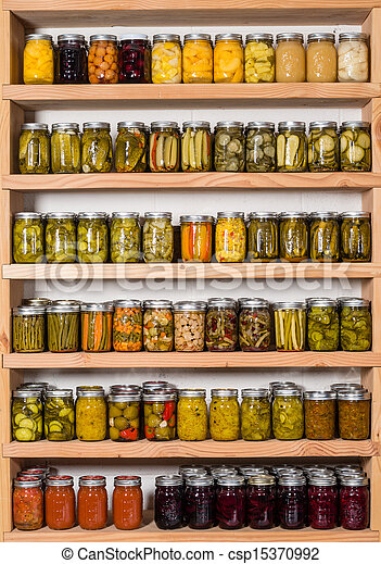 Storage sheves in pantry with homemade canned preserved fruits and vegetables