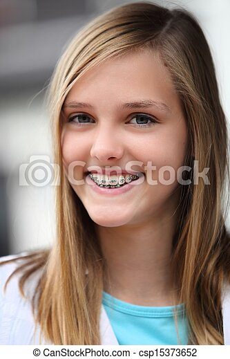 Smiling teenage girl wearing dental braces - csp15373652
