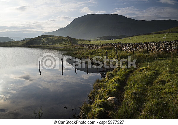 Beautiful sunrise mountain landscape reflected in calm lake - csp15377327