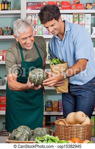 Salesman Assisting Male Customer In Shopping Vegetables - csp15382945