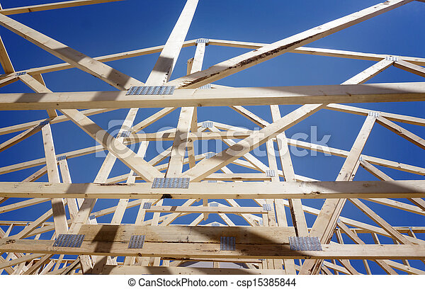 New residential construction home framing against a blue sky and sun  - csp15385844