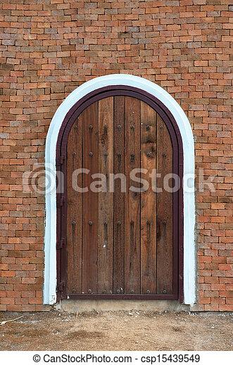 arch wooden door with brick building - csp15439549