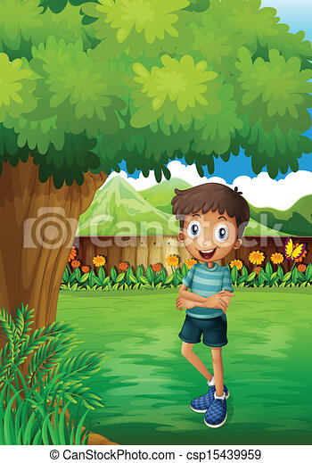 A smiling young man near the tree inside the gated yard - csp15439959