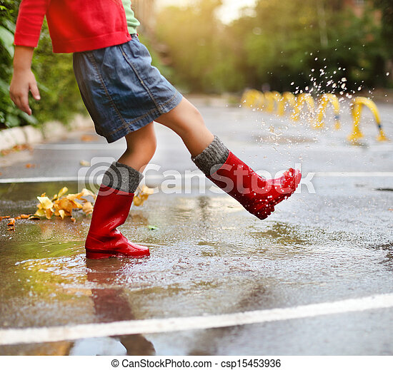 Child wearing red rain boots jumping into a puddle - csp15453936