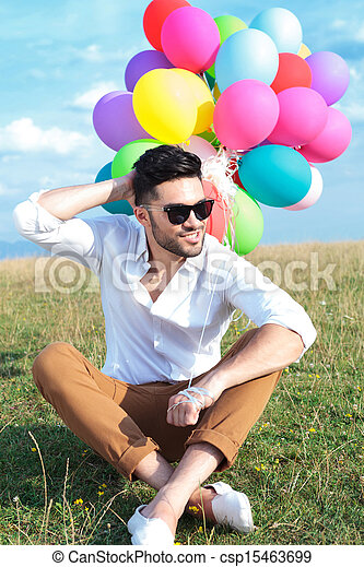 seated casual man with balloons scratches head