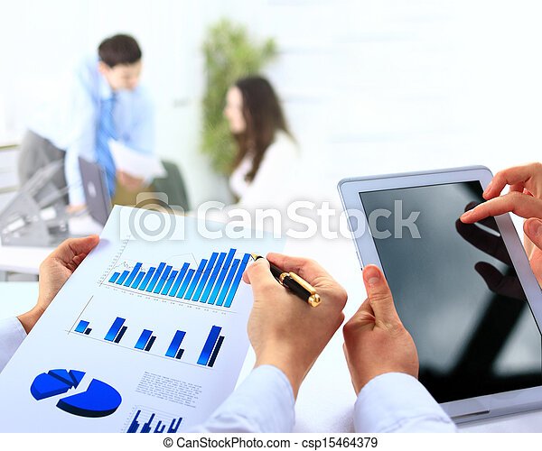 Business work-group analyzing financial data in office - csp15464379