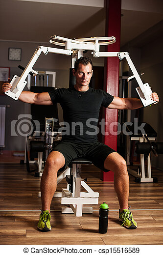 Active sportsman works out in fitness on butterfly machine - csp15516589