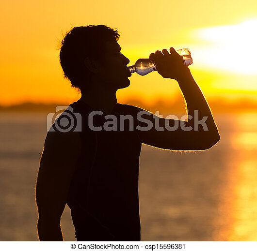 Man drinking bottle of water on the beach at sunrise - csp15596381