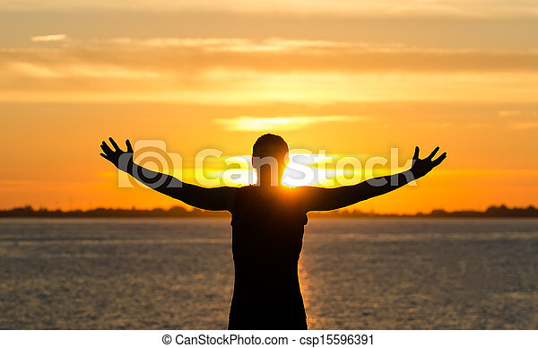 Man with arms wide open on the beach at sunrise - csp15596391