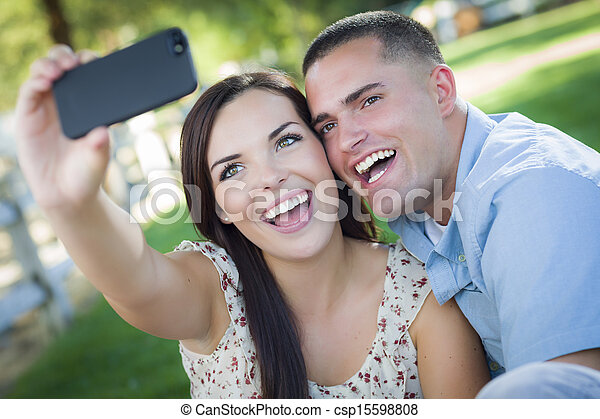 Mixed Race Couple Taking Self Portrait in Park - csp15598808