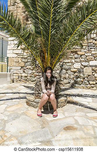 sad girl sitting on the bottom of a palm tree