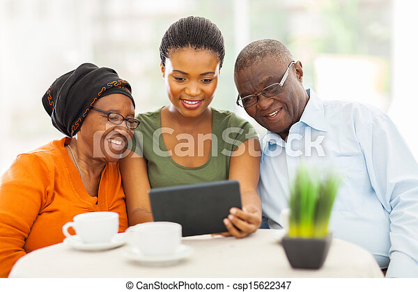 pretty young adult african girl with senior parents using tablet computer - csp15622347