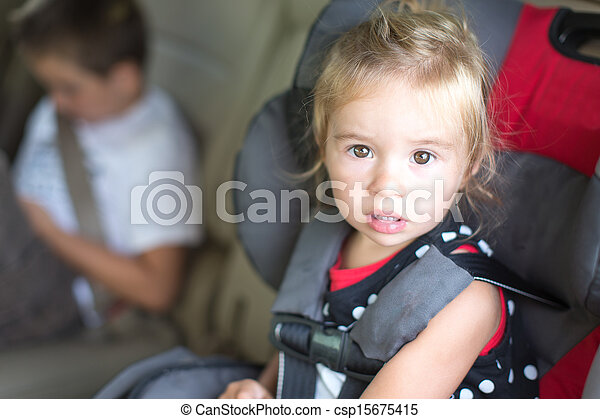 Little girl strapped into a childs safety seat - csp15675415