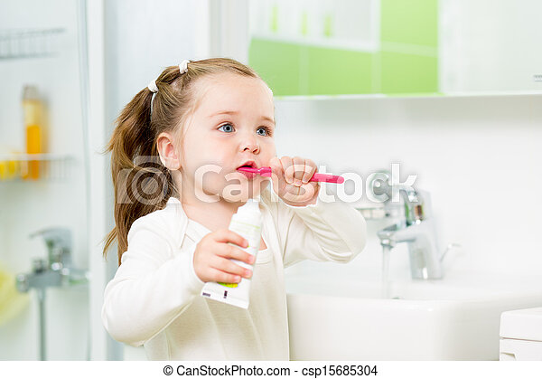 Child girl brushing teeth in bathroom - csp15685304