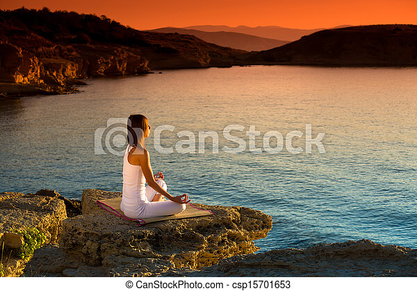Woman making yoga figure on the beach at beautiful sunrise - csp15701653