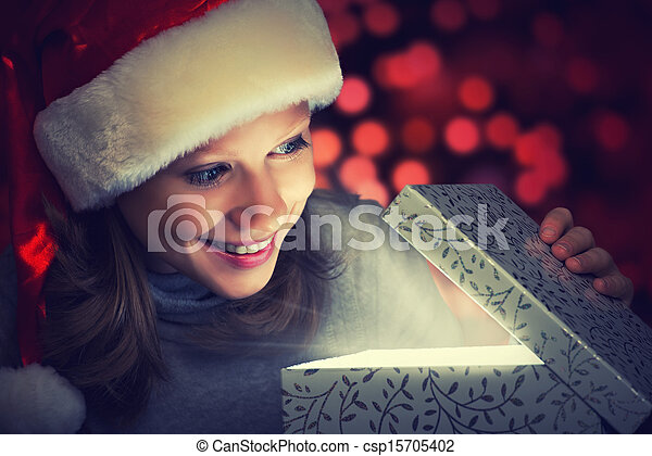 happy woman in a Christmas cap opens the magic box - csp15705402