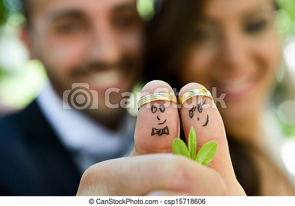 wedding rings on their fingers painted with the bride and groom - csp15718606