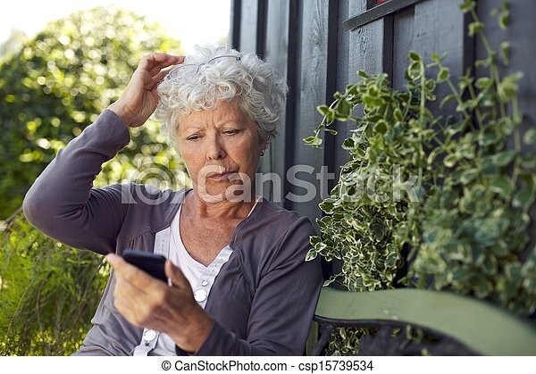 Elder woman reading text message on her cell phone - csp15739534