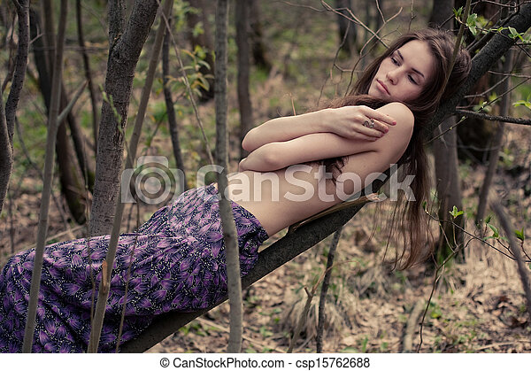Young woman topless hiding her naked chests under her arms in a forest - csp15762688