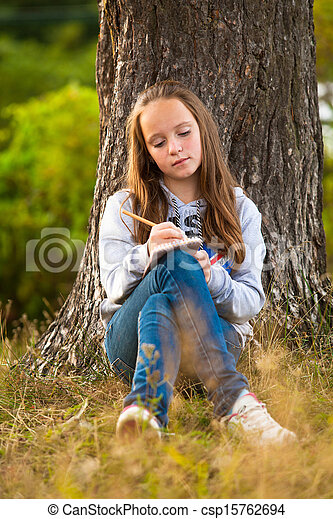 Teen-girl writing in a notebook while sitting in the park - csp15762694