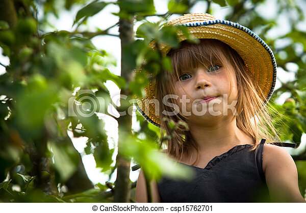 Little lovely girl posing in a straw hat in the park - csp15762701