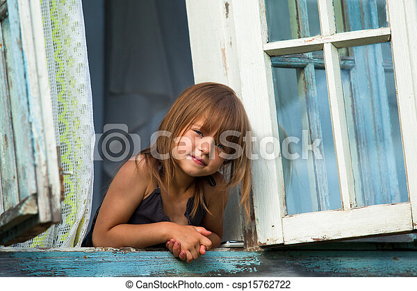 Little girl looks out the window rural house. - csp15762722