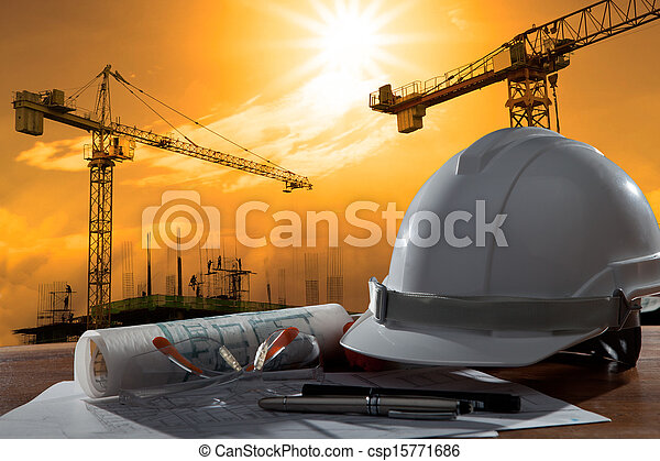 file of safety helmet and architect pland on wood table with sunset scene and building construction - csp15771686