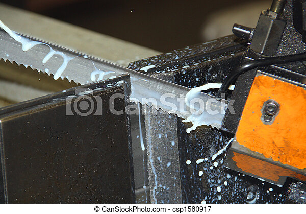 Frozen action shot of bandsaw blade showing teeth and coolant - csp1580917