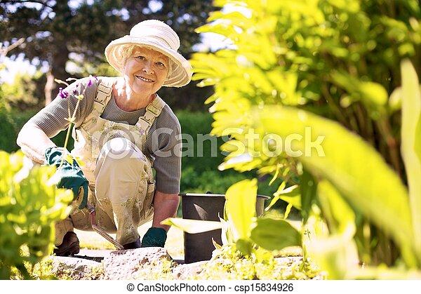Happy elder woman working in her garden - csp15834926