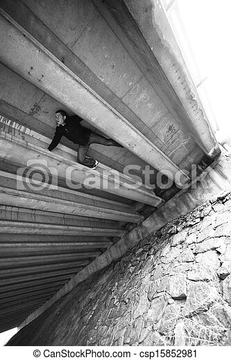 Man doing some Parkour under a bridge structure