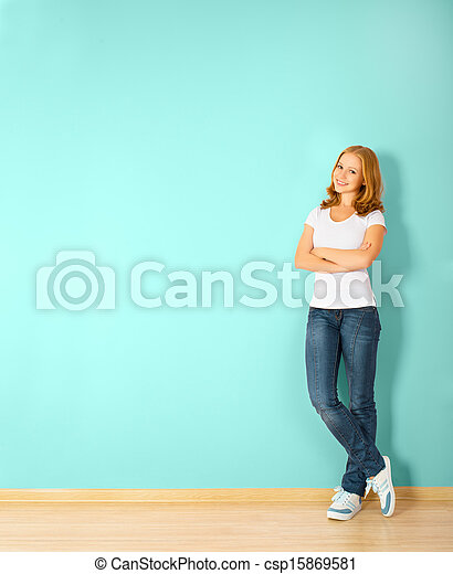 happy  woman is standing in a room with a blank wall - csp15869581