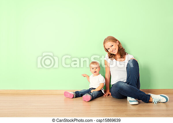 happy family of mother and child is a toddler sitting on the floor in an empty home wall in the room - csp15869639