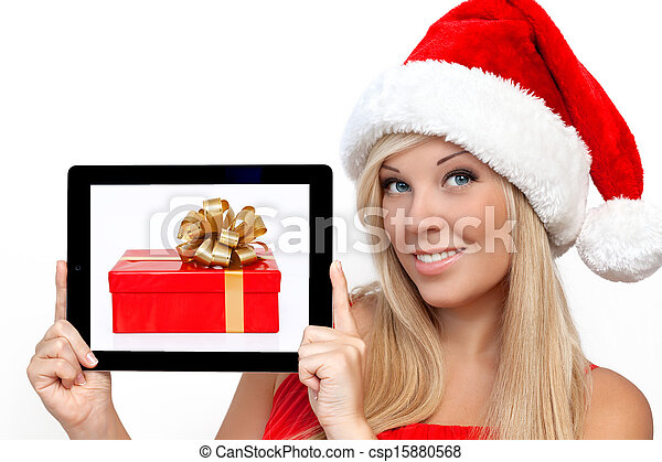 blonde girl in a red Christmas hat on New Year, holding tablet computer touch pad gadget with the gift box on a screen - csp15880568
