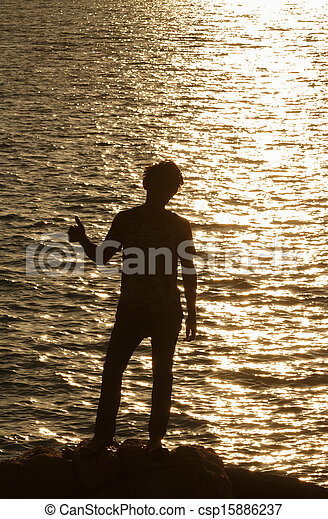 Man silhouette in victory action over sea sunset