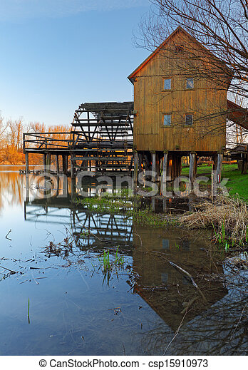 Historic wooden watermill with reflection. - csp15910973