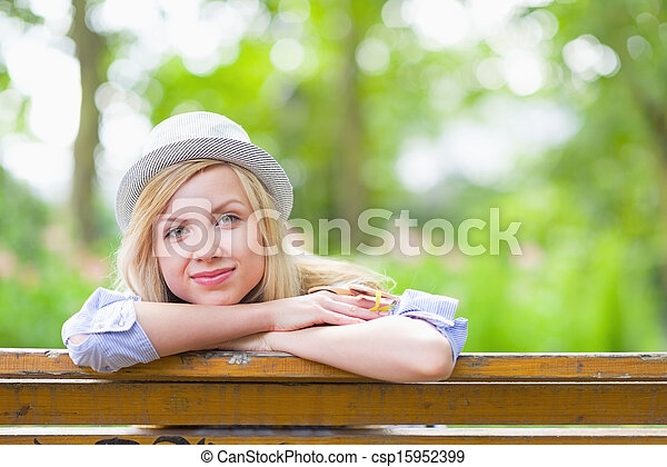 Happy hipster girl sitting in the park - csp15952399