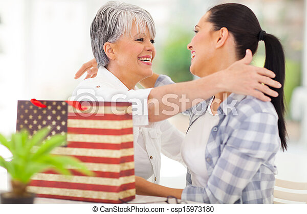 senior woman receiving a gift from adult daughter - csp15973180