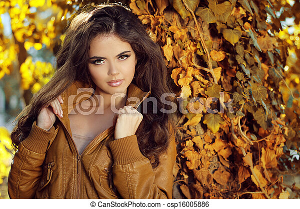 Beautiful elegant woman standing in a park in autumn, outdoors portrait  - csp16005886