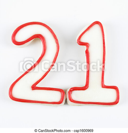 Sugar cookies in the shape of the number twenty one outlined in red icing.