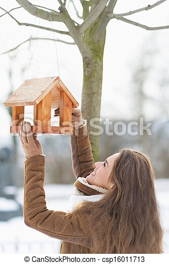 Happy young woman adding meal into bird feeder - csp16011713
