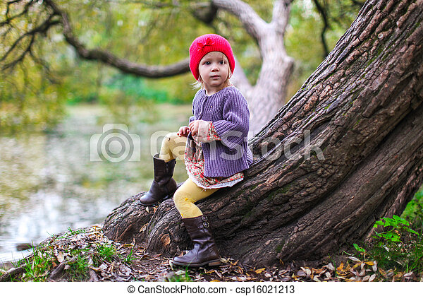 Cute little girl in a red cap near lake at the autumn park - csp16021213