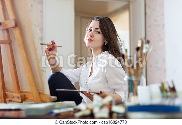 Smiling girl paints on canvas