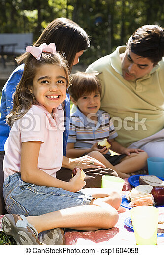 Hispanic girl smiling at viewer with family picnicking in the park.