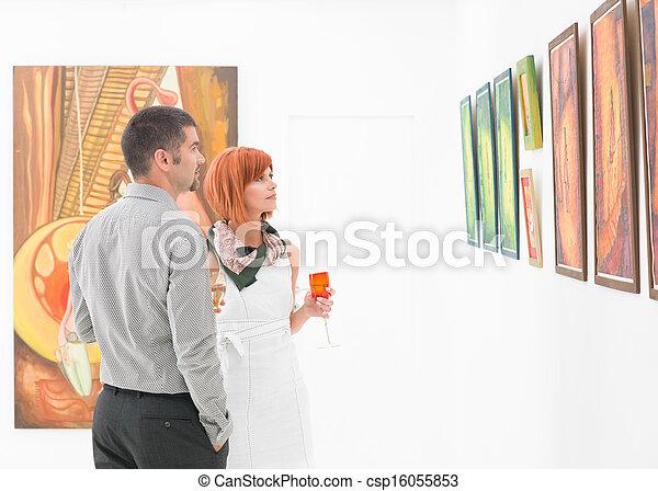 people looking at art gallery paintings - csp16055853