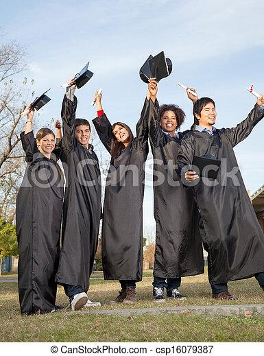 Students With Diplomas Celebrating Success On Graduation Day At - csp16079387