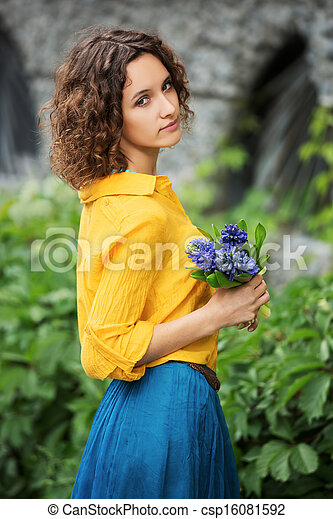 Sad young woman with bouquet of flowers