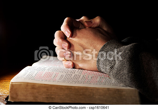 A man\'s hands clasped in prayer over a Holy Bible on a table with dramatic lighting (shallow focus).
